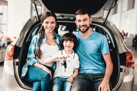 Family Are Sitting In The Trunk Of A New Car. Smiling Customers. Buying In A Showroom. Automobile Salon. Happy Together. Successful Choice. Good Mood. Great Trade. Auto Rewiew. Make A Decision.