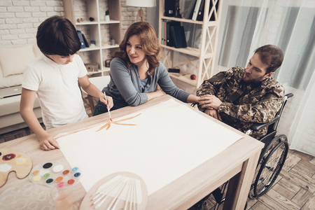 Paralyzed Soldierss Son Is Drawing A Picture. Kid With Tassel. Resting Together. Child And Wife. Camouflage Uniform. Feelings Showing. Home Leisure. Disabled Veteran. Watercolor Painting. Stok Fotoğraf