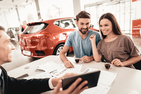 Happy Young Family Are Choosing A New Car In Showroom. Dialogue With Dealer. Cheerful Customer. Automobile Salon. Make A Decision. Cup Of Coffee. End Of A Deal. Good Offer. Information On Tablet. Foto de archivo - 107722142