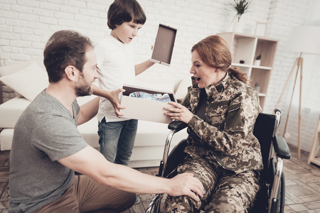 Woman Veteran In Wheelchair Homecoming Concept. Family Meeting. Son And Husband. Box With A Gift. Camouflage Uniform. Child Hanging. Feelings Showing. Patriotic Comeback. Paralyzed Soldier.