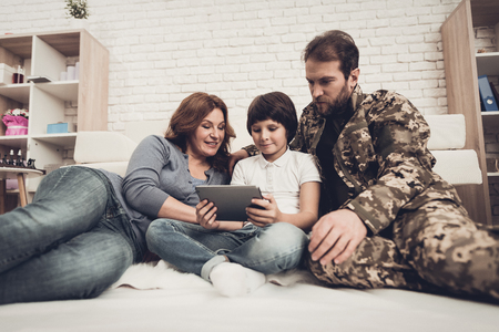 Disabled Man In A Wheelchair Watch A Tablet With Family. Meeting After War. Son And Wife. Camouflage Uniform. Feelings Showing. Return From Army. Paralyzed Soldier. Homecoming Concept. Banque d'images - 107722143