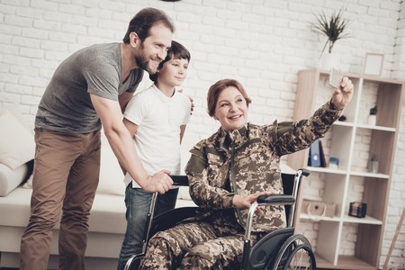 Disabled Woman In A Wheelchair Makes A Selfie With Family. Meeting After War. Son And Husband. Camouflage Uniform. Feelings Showing. Return From Army. Paralyzed Soldier. Homecoming Concept. Stock Photo