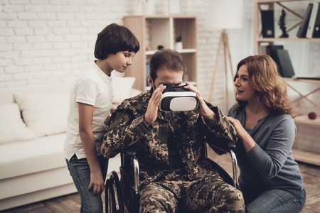 Paralyzed Male Soldier Family Are Having Fun. Meeting After War. Son And Wife. Camouflage Uniform. Virtual Reality Glasses. Paralyzed Soldier. Homecoming Concept. Return From Army.