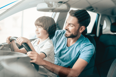 Man With Kid Are Sitting At The Wheel Of New Vehicle. Smiling Family. Car Buying In A Showroom. Automobile Salon. Cheerful Driver. Happy Together. Father And Son. Good Mood. Great Trade. 스톡 콘텐츠