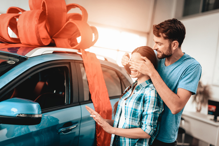 A Guy Shows A New Car To Girlfriend. Present Concept. Staring At Each Other. Automobile Salon. Make A Decision. Gift Ribbon. Eyes Closed. Good Offer. Happy Together. Successful Buying.