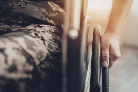 Disabled Soldier In A Wheelchair. Disability Problem. After War Concept. Camouflage Uniform. Paralyzed Woman. Home Leisure. Return From Army. Hands On Wheels. Suffering From A Pain.