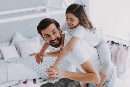 Cute Young Daughter on Piggy Back Ride with Dad. Happy Fathers Day Concept. Father with Daughter Spending Time Togetherness at Home. Happy Family Daughter Laughs on Holiday