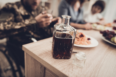 A Veteran In A Wheelchair Sitting With Glass Of Whiskey. Meeting Concept. Family Background. Camouflage Uniform. Drink Too Much. Bottle Of Alcohol. Paralyzed Soldier. Depression Problem. Banque d'images - 107998978