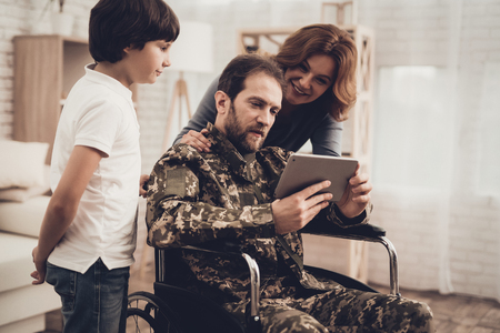 Disabled Man In A Wheelchair Watch A Tablet With Family. Meeting After War. Son And Wife. Camouflage Uniform. Feelings Showing. Return From Army. Paralyzed Soldier. Homecoming Concept. Banque d'images - 107792259