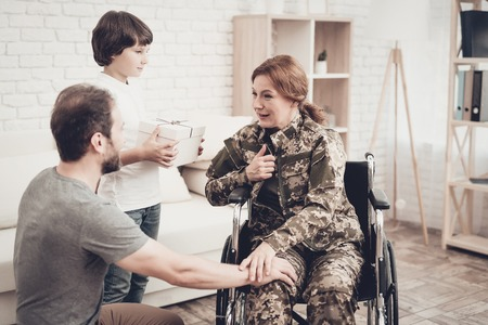 Woman Veteran In Wheelchair Homecoming Concept. Family Meeting. Son And Husband. Box With A Gift. Camouflage Uniform. Child Hanging. Feelings Showing. Patriotic Comeback. Paralyzed Soldier. Banque d'images - 107792260