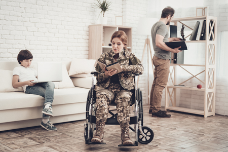 Disabled Soldier Woman In Wheelchair Book Reading. Meeting After War. Son And Husband. Camouflage Uniform. Family Concept. Paralyzed Soldier. Home Lifestyle Leisure. Return From Army.