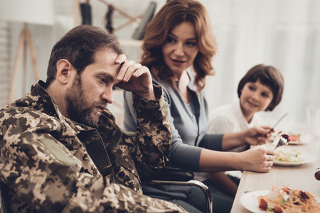 A Veteran In A Wheelchair Dinner With Family. Meeting Concept. Son And Wife. Camouflage Uniform. Resting Together. Feelings Showing. Patriotic Comeback. Paralyzed Soldier. Depression Problem.