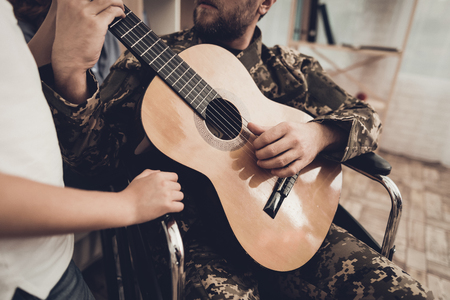 Veteran In The Wheelchair Guitar Play Concept. Family Meeting. Son And Wife. Camouflage Uniform. Family Background. Resting Together. Feelings Showing. Patriotic Comeback. Paralyzed Soldier.
