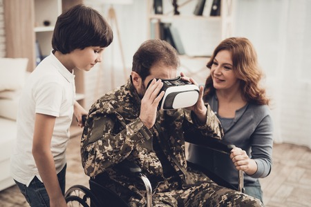 Paralyzed Male Soldier Family Are Having Fun. Meeting After War. Son And Wife. Camouflage Uniform. Virtual Reality Glasses. Paralyzed Soldier. Homecoming Concept. Return From Army. Banque d'images - 107862459
