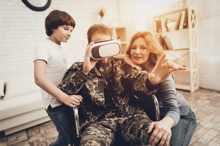 Paralyzed Male Soldier Family Are Having Fun. Meeting After War. Son And Wife. Camouflage Uniform. Virtual Reality Glasses. Paralyzed Soldier. Homecoming Concept. Return From Army. Banque d'images - 107792465