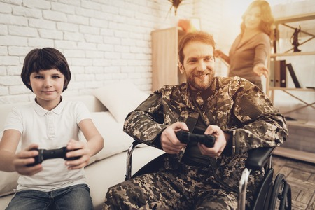 Paralyzed Male Soldier Plays Console With Sun. Family Meeting. Son And Wife. Homecoming Concept. Camouflage Uniform. Child Hanging. Feelings Showing. Patriotic Comeback. Paralyzed Soldier. Banque d'images - 107753691