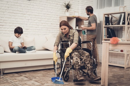Female Veteran In A Wheelchair Is Cleaning House. Supporting Husband. Camouflage Uniform. Disabled Soldier. Family Concept. Working Together. Holiday Leisure. Yellow Gloves. Free Time.