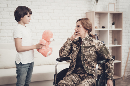 Woman Veteran In Wheelchair Homecoming Concept. Family Meeting. Leaving From War. Fluffy Toy. Camouflage Uniform. Son Hanging. Feelings Showing. Patriotic Comeback. Paralyzed Soldier. Banque d'images - 107734848