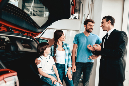 Happy Young Family Are Choosing A New Auto In Showroom. Dialogue With Dealer. Cheerful Customer. Look Inside The Trunk. Make A Decision. Good Offer. Buyer And Seller. Business Trade.
