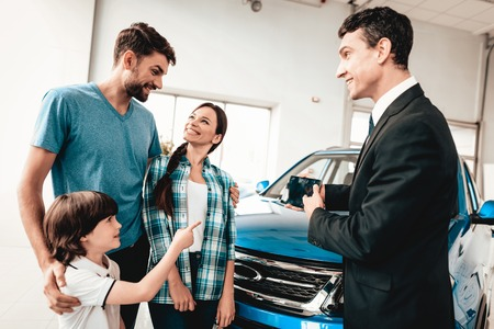 Happy Young Family Are Choosing A New Car In Showroom. Dialogue With Dealer. Cheerful Customer. Automobile Salon. Make A Decision. Information On Tablet. Good Offer. Buyer And Seller. Business Trade. 스톡 콘텐츠