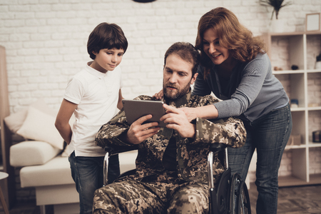 Disabled Man In A Wheelchair Watch A Tablet With Family. Meeting After War. Son And Wife. Camouflage Uniform. Feelings Showing. Return From Army. Paralyzed Soldier. Homecoming Concept.