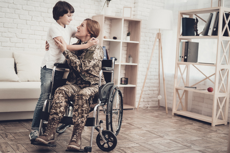 Woman Veteran In Wheelchair Homecoming Concept. Family Meeting. Leaving From War. Embrace With Child. Camouflage Uniform. Son Hanging. Feelings Showing. Patriotic Comeback. Paralyzed Soldier.
