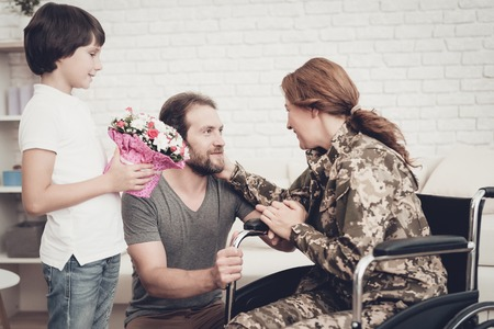 Woman Veteran In Wheelchair Homecoming Concept. Family Meeting. Son And Husband. Embrace With Mother. Camouflage Uniform. Child Hanging. Flowers Bouquet. Patriotic Comeback. Paralyzed Soldier. Banque d'images - 107862464