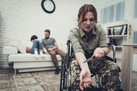 Depressed Paralyzed Veteran Comitting A Suicide. Family Background. Camouflage Uniform. Veins Cutting. Disappointed Hero. Paralyzed Soldier. Psychical Problem. Posttraumatic Syndrome. Knife In Hand.