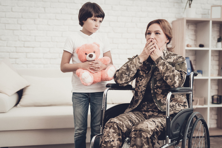 Woman Veteran In Wheelchair Homecoming Concept. Family Meeting. Leaving From War. Fluffy Toy. Camouflage Uniform. Son Hanging. Feelings Showing. Patriotic Comeback. Paralyzed Soldier. Banque d'images - 107753701