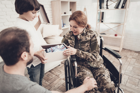 Woman Veteran In Wheelchair Homecoming Concept. Family Meeting. Son And Husband. Box With A Gift. Camouflage Uniform. Child Hanging. Feelings Showing. Patriotic Comeback. Paralyzed Soldier. Stock Photo - 107753702