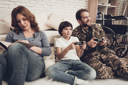 Paralyzed Male Soldier Plays Console With Sun. Family Meeting. Son And Wife. Homecoming Concept. Camouflage Uniform. Child Hanging. Feelings Showing. Patriotic Comeback. Paralyzed Soldier.