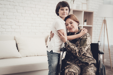 Woman Veteran In Wheelchair Homecoming Concept. Family Meeting. Leaving From War. Embrace With Child. Camouflage Uniform. Son Hanging. Feelings Showing. Patriotic Comeback. Paralyzed Soldier. Banque d'images - 107792595