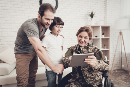 Disabled Woman In A Wheelchair Watch A Tablet With Family. Meeting After War. Son And Husband. Camouflage Uniform. Feelings Showing. Return From Army. Paralyzed Soldier. Homecoming Concept. Zdjęcie Seryjne