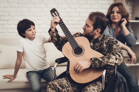 Veteran In The Wheelchair Guitar Play Concept. Family Meeting. Son And Wife. Camouflage Uniform. Family Background. Resting Together. Feelings Showing. Patriotic Comeback. Paralyzed Soldier. Banque d'images - 107862470