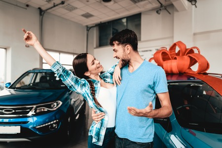 A Guy Shows A New Car To Girlfriend. Present Concept. Staring At Each Other. Automobile Salon. Make A Decision. Gift Ribbon. End Of A Deal. Good Offer. Happy Together. Successful Buying.