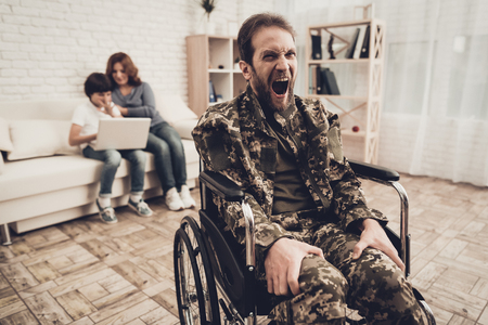 Disabled Soldier In Wheelchair. Suffering From Pain. Meeting After War. Son And Wife Background. Camouflage Uniform. Family Concept. Paralyzed Hero. Home Leisure. Return From Army.