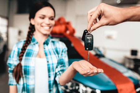 A Guy Gives A Car Key To Girlfriend. Present Concept. Automobile Salon. Make A Decision. Gift Ribbon. End Of A Deal. Good Offer. Happy Together. Successful Buying. Beautiful Surprise.