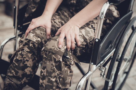 Disabled Soldier In A Wheelchair. Disability Problem Concept. After War. Camouflage Uniform. Paralyzed Woman. Home Leisure. Return From Army. Hands On Knees. Suffering From A Pain.
