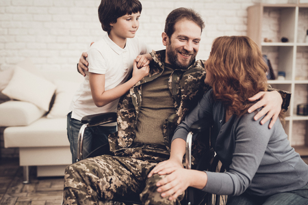 Male Veteran In Wheelchair Homecoming Concept. Home Meeting. Son And Wife. Embrace With Family. Camouflage Uniform. Child Hanging. Heroic Comeback. Paralyzed Soldier. Disabled Man. Banque d'images - 107792600