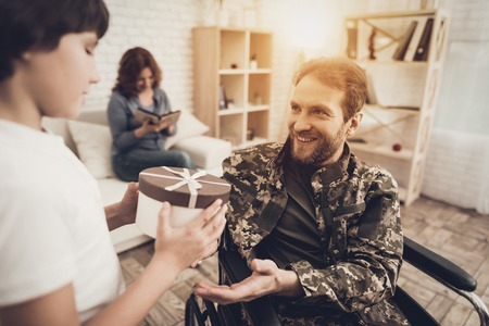 Man Veteran In Wheelchair Homecoming Concept. Family Meeting. Son And Wife. Box With A Gift. Camouflage Uniform. Child Hanging. Feelings Showing. Patriotic Comeback. Paralyzed Soldier. Banque d'images - 107862496