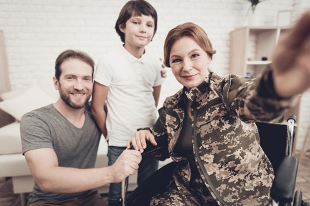 Disabled Woman In A Wheelchair Makes A Selfie With Family. Meeting After War. Son And Husband. Camouflage Uniform. Feelings Showing. Return From Army. Paralyzed Soldier. Homecoming Concept. Banque d'images - 107862499