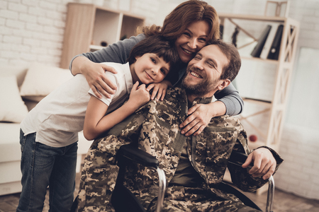 Male Veteran In Wheelchair Homecoming Concept. Home Meeting. Son And Wife. Embrace With Family. Camouflage Uniform. Child Hanging. Heroic Comeback. Paralyzed Soldier. Disabled Man. Banque d'images - 107792602
