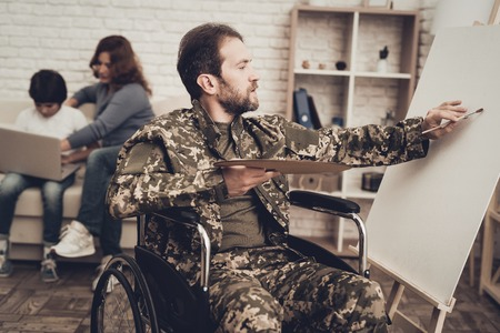 Disabled Soldier In Wheelchair Draws A Picture. After War Concept. Camouflage Uniform. Paralyzed Man With A Tassel. Home Relaxing. Return From Army. Family Background. Wife And Son.