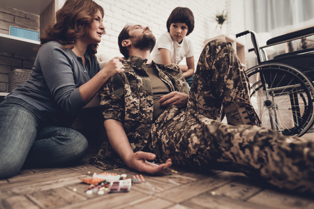 Disable Veteran Lays On Floor. Narcotic Overdose. Syringe In Hand. Pills On The Floor. Frightened Family. Camouflage Uniform. Disappointed Hero. Paralyzed Soldier. Depression Problem. Stockfoto