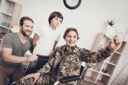 Disabled Woman In A Wheelchair Makes A Selfie With Family. Meeting After War. Son And Husband. Camouflage Uniform. Feelings Showing. Return From Army. Paralyzed Soldier. Homecoming Concept. Banque d'images - 107837866