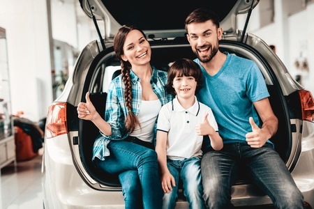 Family Are Sitting In The Trunk Of A New Car. Thumbs Up. Buying In A Showroom. Automobile Salon. Happy Together. Successful Choice. Good Mood. Great Trade. Auto Rewiew. Make A Decision.