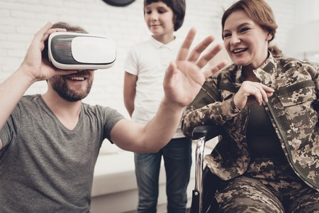 Disabled Woman Soldier Family Are Having Fun. Meeting After War. Son And Husband. Camouflage Uniform. Virtual Reality Glasses. Paralyzed Soldier. Homecoming Concept. Return From Army.