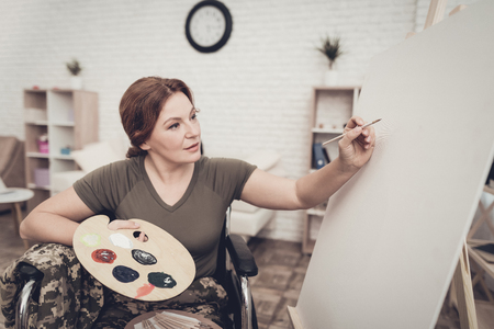Disabled Soldier In A Wheelchair Draws A Picture. After War Concept. Camouflage Uniform. Paralyzed Woman With Tassel. Home Leisure. Return From Army. Watercolor Paints. Holiday Joy. Banque d'images - 107837872