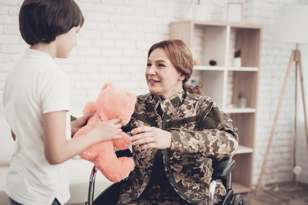 Woman Veteran In Wheelchair Homecoming Concept. Family Meeting. Leaving From War. Fluffy Toy. Camouflage Uniform. Son Hanging. Feelings Showing. Patriotic Comeback. Paralyzed Soldier. Banque d'images - 107837875
