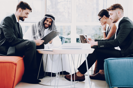 Arabian Businessman Discussion Meeting With Partners. Money Investment. Paper Documents. Talking With Managers. Partnership Agreement. Disdash And Keffiyeh Wearing. Work With Laptop. Фото со стока